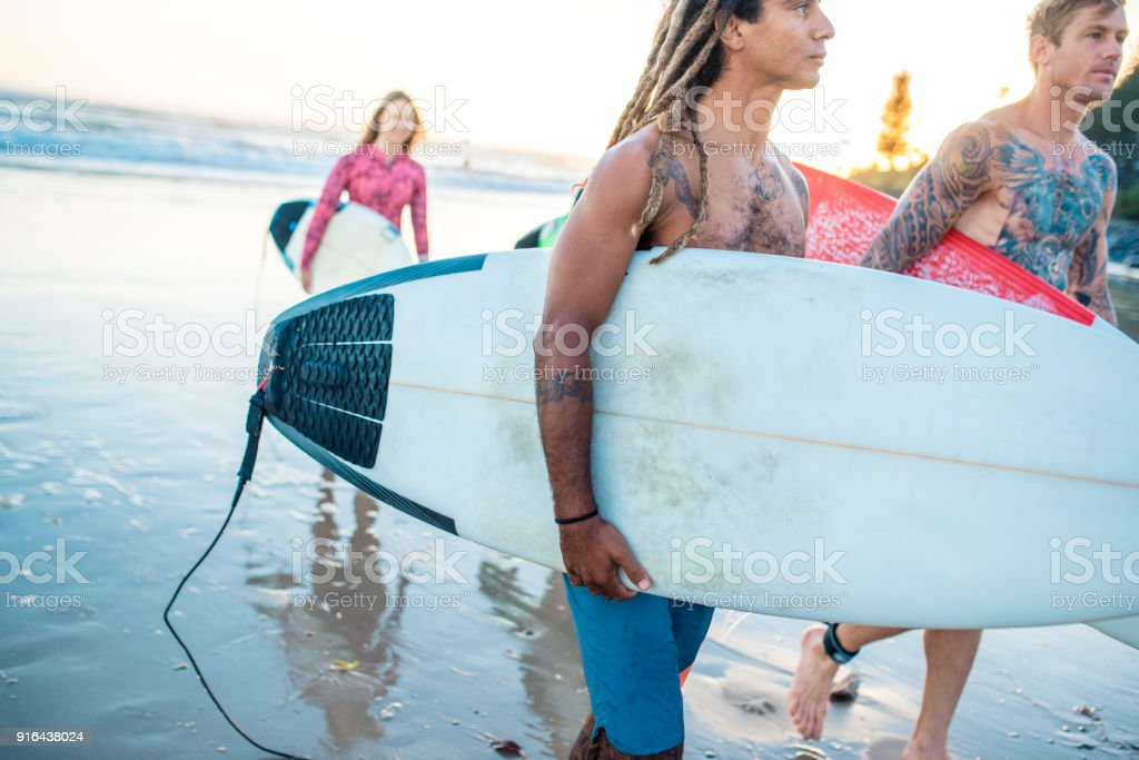 Friends getting out of water with surfboards at sunset stock photo