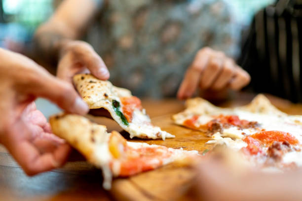 Friends getting slices of pizza, using hands stock photo
