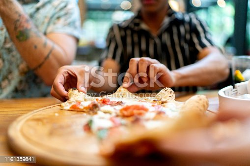 Friends getting slices of pizza, using hands
