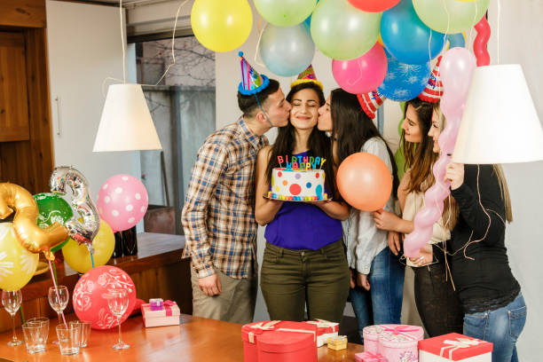 Friends give a birthday cake to their friend Teenagers celebrate birthday group of friends giving gifts to the birthday girl stock pictures, royalty-free photos & images