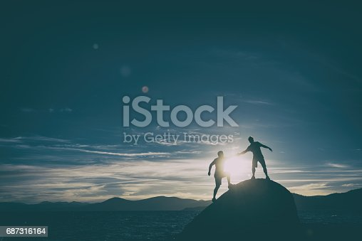 istock friends giving each other a hand in the mountains 687316164