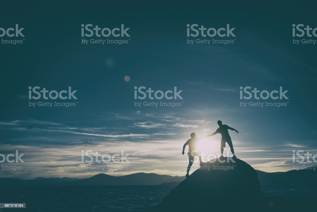 friends giving each other a hand in the mountains stock photo