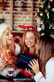 istock Friends giving gifts to each other and drinking wine. 1053343268