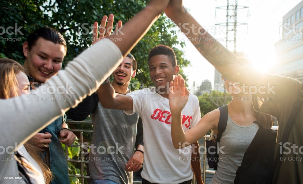 Friends giving high fives stock photo