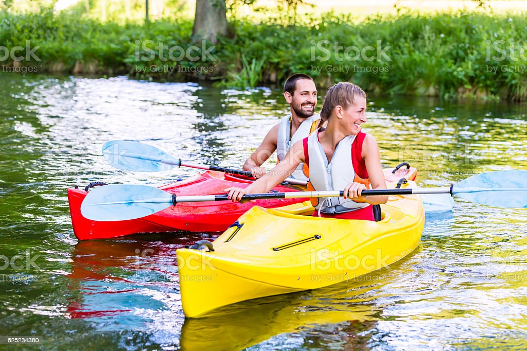 Friends going down river in sport canoe stock photo