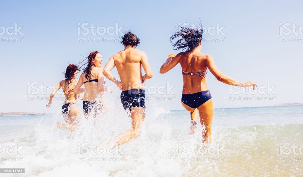 Friends going into the sea stock photo