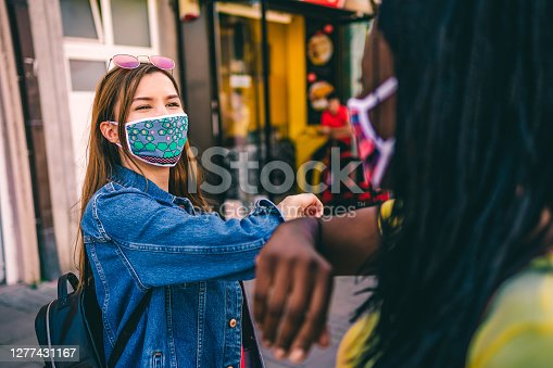 Female friends practicing alternative greeting to avoid handshakes during COVID-19 pandemic, elbow bump