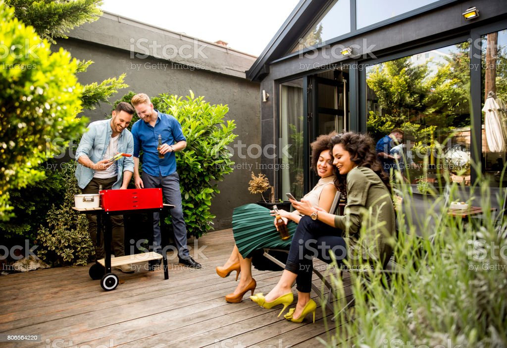 Friends grilling food and enjoying barbecue party outdoors stock photo
