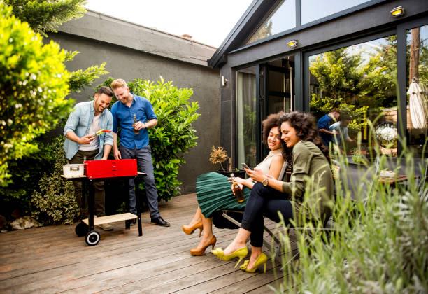 freunden grillen der speisen und genießen grillfest im freien - grillen garten stock-fotos und bilder