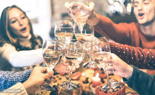 1064325668 istock photo Friends group celebrating Christmas toasting champagne wine at home dinner - Winter holiday concept with young people enjoying time and having fun together - Azure vintage filter with focus on glasses 1073492734