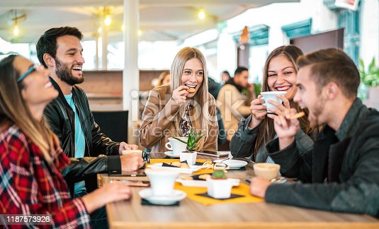 istock Friends group drinking cappuccino at coffee bar - People talking and having fun together at fancy cafeteria - Friendship concept with happy guys and girls at restaurant cafe - Warm bulb light filter 1187573926