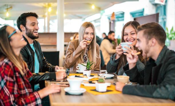 grupa przyjaciół pijących cappuccino w kawiarni - ludzie rozmawiają i bawią się razem w fantazyjnej kawiarni - koncepcja przyjaźni z szczęśliwymi facetami i dziewczynami w kawiarni restauracyjnej - ciepły filtr żarówki - przyjaźń zdjęcia i obrazy z banku zdjęć