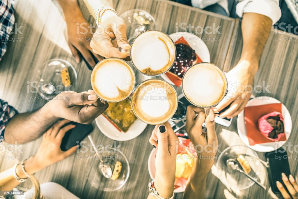 Friends group drinking cappuccino at coffee bar restaurant - People hands toasting at fashion cafeteria with upper view point - Winter drinks concept with men and women at cafe - Warm vintage filter royalty-free stock photo