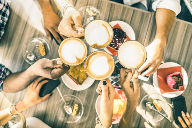 friends group drinking cappuccino at coffee bar restaurant - people hands toasting at fashion cafeteria with upper view point - winter drinks concept with men and women at cafe - warm vintage filter - family meeting stock photos and pictures