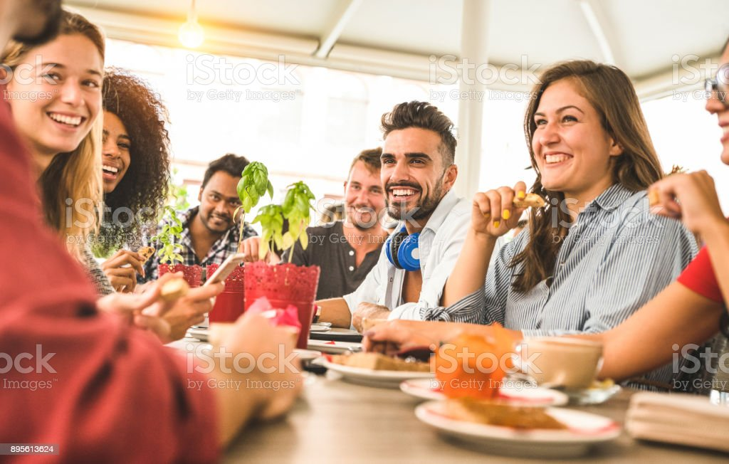 Friends group drinking cappuccino at coffee bar restaurant - People talking and having fun together at fashion cafeteria - Friendship concept with happy men and women at cafe - Warm vintage filter stock photo