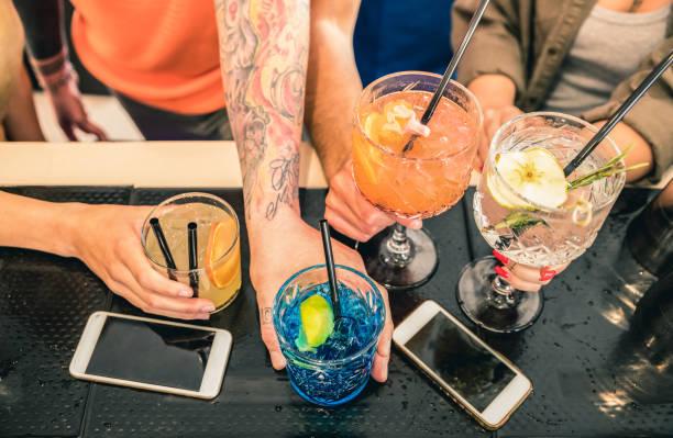 freunde gruppe fashion bar restaurant - high angle view punkt der menschen hände auf mobilen smartphones - soziale sammeln konzept mit betrunkenen jungs und mädels - vivid teal orange filter cocktail trinken - freundin tattoos stock-fotos und bilder