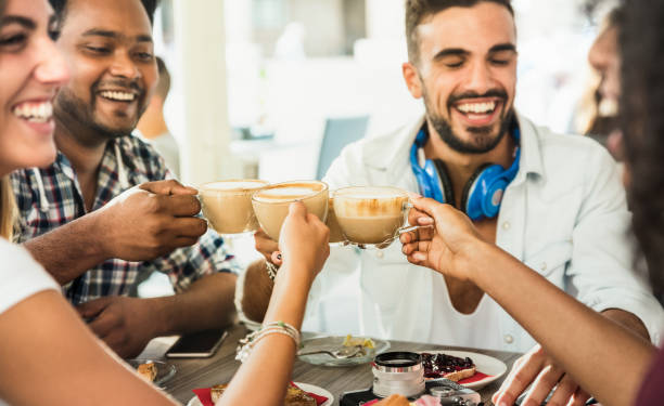 Friends group drinking latte at coffee bar restaurant - People talking and having fun together at fashion cafeteria - Friendship concept with happy men and women at cafe - Focus on cappuccino cups stock photo