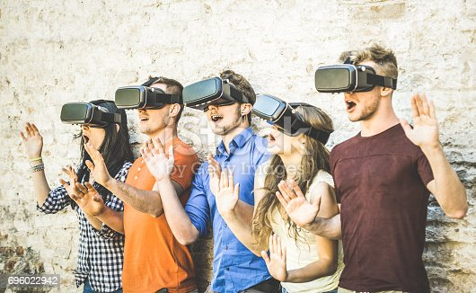 istock Friends group playing on vr glasses outdoors - Virtual reality and wearable tech concept with young people having fun together with headset goggles - Digital generation trends - Retro contrast filter 696022942