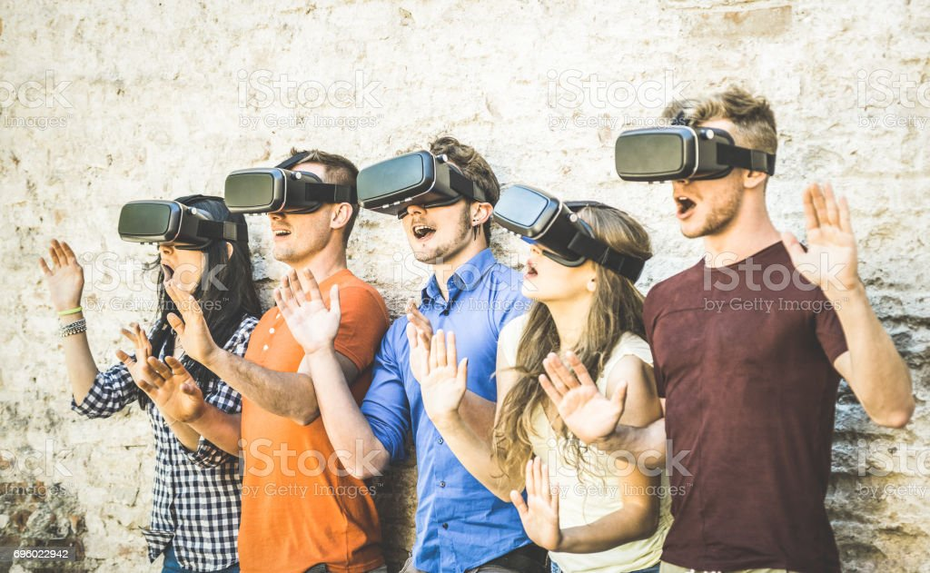 Friends group playing on vr glasses outdoors - Virtual reality and wearable tech concept with young people having fun together with headset goggles - Digital generation trends - Retro contrast filter stock photo