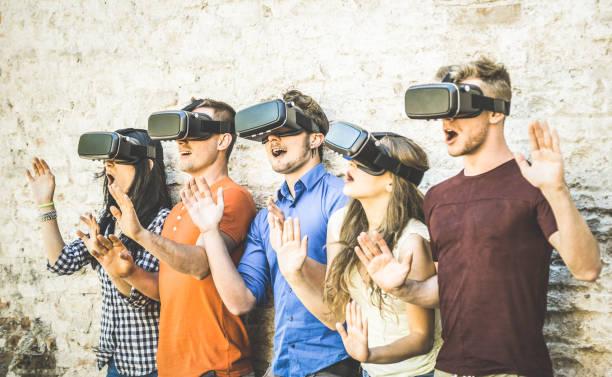 Vr メガネ アウトドア - バーチャル ・ リアリティとヘッドセットと一緒に楽し若者とウェアラブル技術コンセプトで遊んで友達グループ ゴーグル - デジタル世代の動向 - レトロなコントラスト フィルター ストックフォト