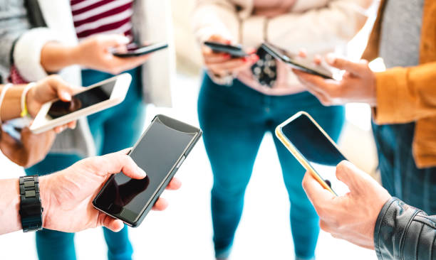 Friends group sharing content on mobile smart phone - Close up of people hands using tracking app with social media network - Technology concept with always connected millenials - Vivid bright filter stock photo