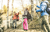 Friends group trekking in forest on french alps at sunset - Hikers with backpacks and sticks walking on mountain woods - Wanderlust travel concept with young people at excursion - Focus on left guy