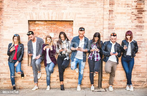 911294484istockphoto Friends group using smartphone against wall at university college backyard break - Young people addicted by mobile smart phone - Technology concept with always connected millennials - Filter image 952414248