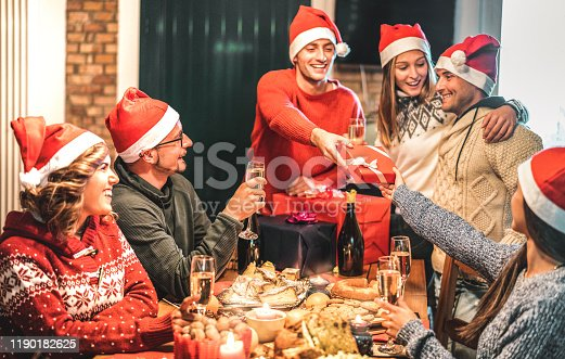 1064325668 istock photo Friends group wearing santa hat giving each other Christmas presents - Champagne wine toast at home x mas dinner - Holiday concept with young people sharing time together and having fun on winter time 1190182625