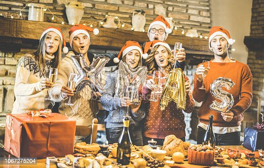 1064325668 istock photo Friends group with santa hat celebrating Christmas time with champagne and sweets food at dinner party - Winter holiday concept with people enjoying each other having fun eating together - Warm filter 1067275204
