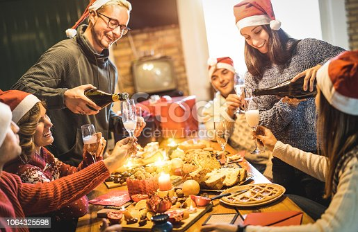 1064325668 istock photo Friends group with santa hats celebrating Christmas with champagne and sweets food at home dinner - Winter holidays concept with people enjoying time and having fun eating together - Warm filter 1064325598