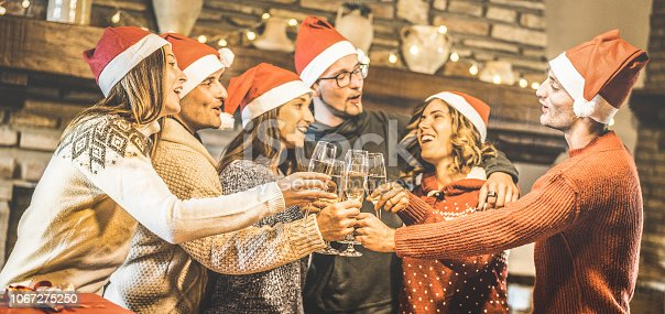 1064325668 istock photo Friends group with santa hats celebrating Christmas with champagne wine toast at home dinner - Winter holidays concept with young people enjoying time and having fun together - Focus on glasses 1067275250
