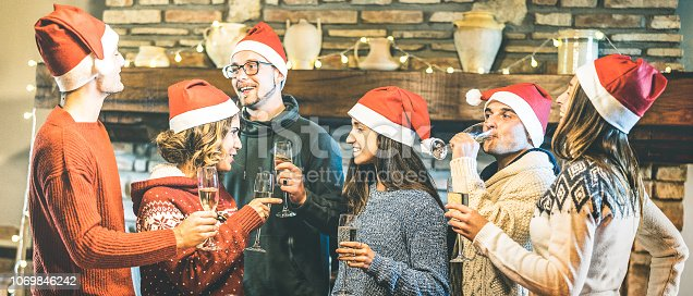1064325668 istock photo Friends group with santa hats celebrating Christmas with champagne wine toast at home dinner - Winter holidays concept with young people talking and having fun together - Focus on middle girl 1069846242