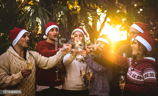 1064325668istockphoto Friends group with santa hats celebrating Christmas with champagne wine toast outdoors - Tropical holidays concept with young people enjoying time and having fun together with sparkles at sunset 1073493024