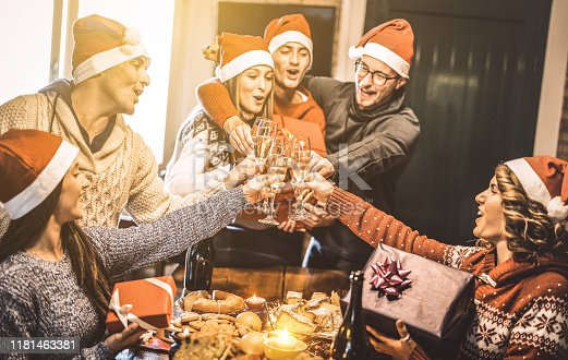 1064325668 istock photo Friends group with santa hats exchanging Christmas presents with champagne wine toast at home dinner - Winter holiday concept with young people enjoying time and having fun together - Focus on glasses 1181463381