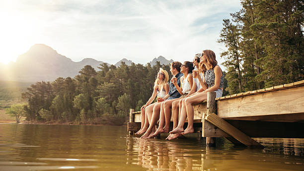 friends hanging out at the lake - rural lifestyle stock photos and pictures