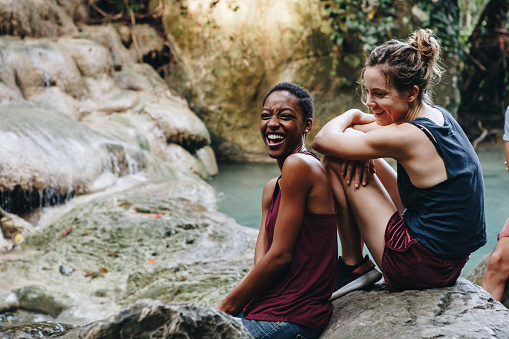 Friends hanging out by a waterfall in the jungle