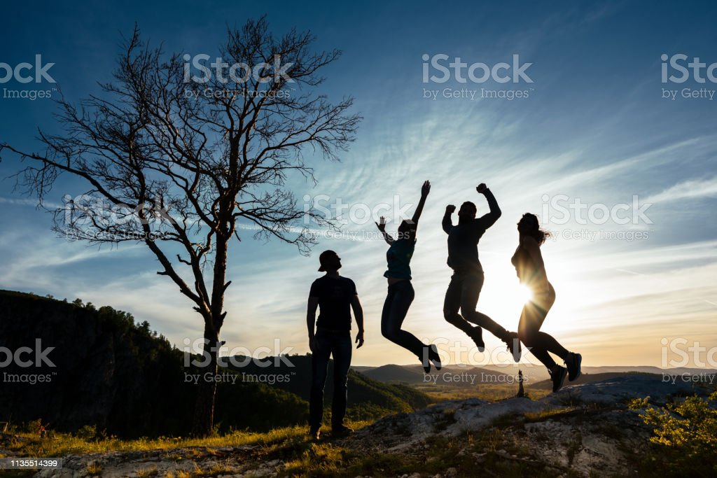 Friends have fun at sunset. Funny friends. A group of people in nature. Silhouettes of friends. Best friend. Friends traveling. Group of people at sunset. People have fun at sunset. Happy people stock photo