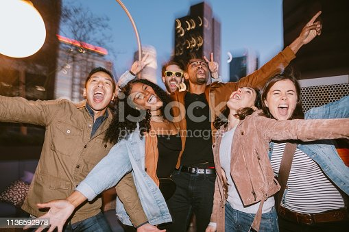 A diverse group of multiethnic friends have a party or celebration outside in downtown Los Angeles, California.  They dance to music, enjoying the the night fun.