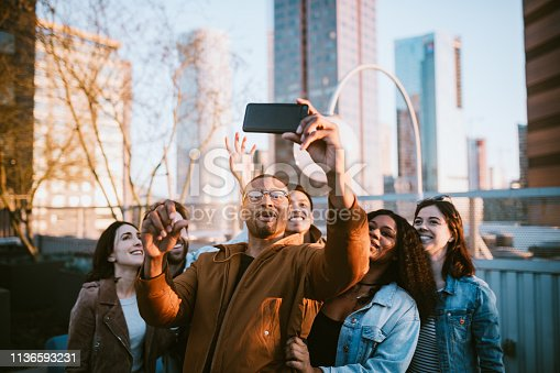 A diverse group of multiethnic friends have a party or celebration outside in downtown Los Angeles, California.  One of them takes a selfie of the group on their smartphone to share on social media.