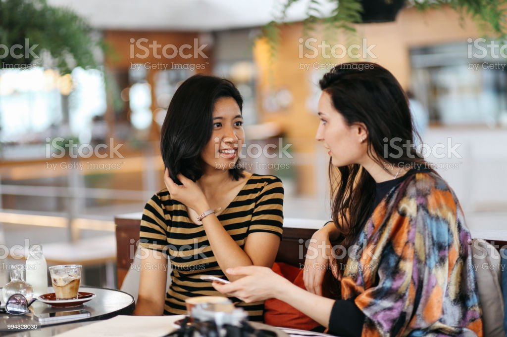 Young girl friends wearing vintage clothes sitting in a cafe or a...