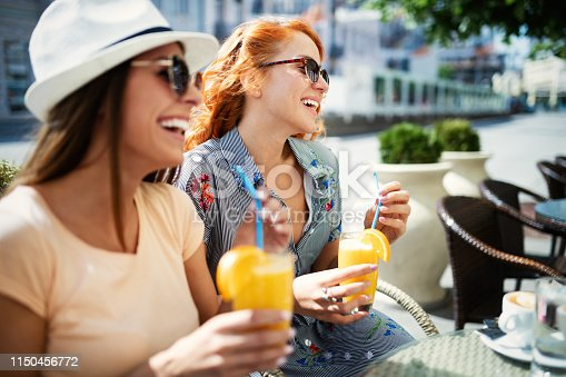 Friends having a great time in cafe . Girls smiling and drinking juice and enjoying together.