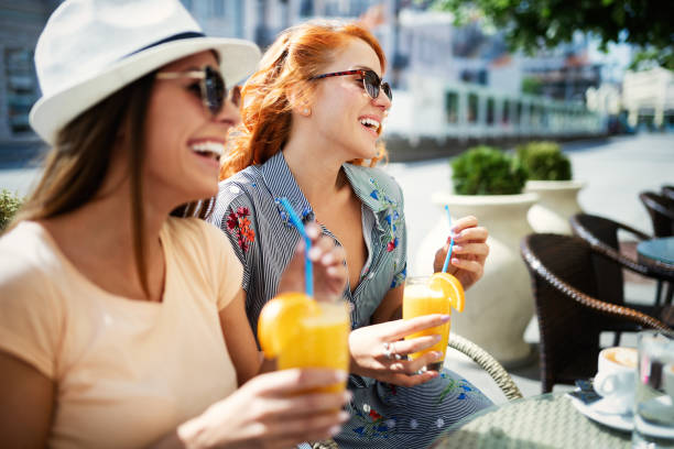 Freunde, die eine tolle Zeit im Café haben. Frauen lächeln und trinken Saft und genießen zusammen – Foto
