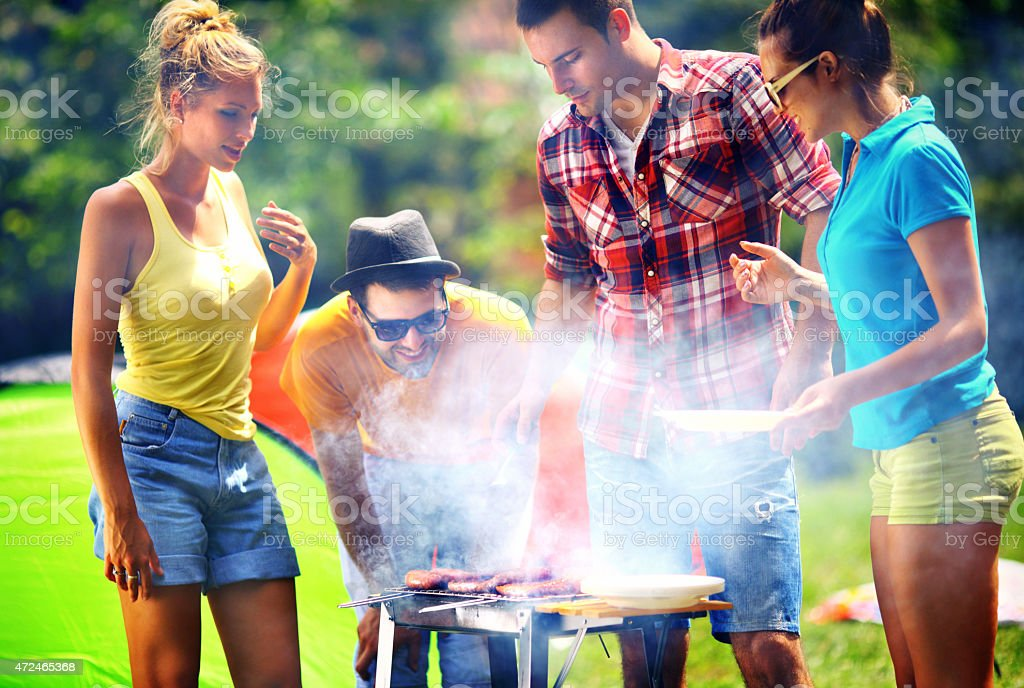 Friends having barbecue party, stock photo