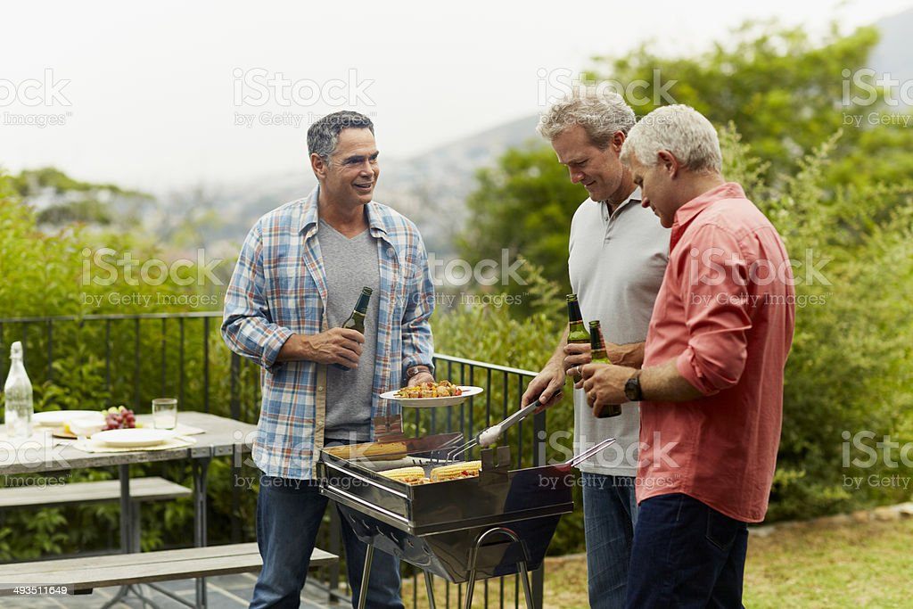 Friends having beer while barbecuing​​​ foto