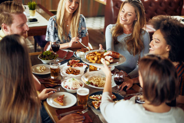 Friends having dinner at restaurant. Friends having dinner at restaurant. Multi ethnic group. restaurants stock pictures, royalty-free photos & images