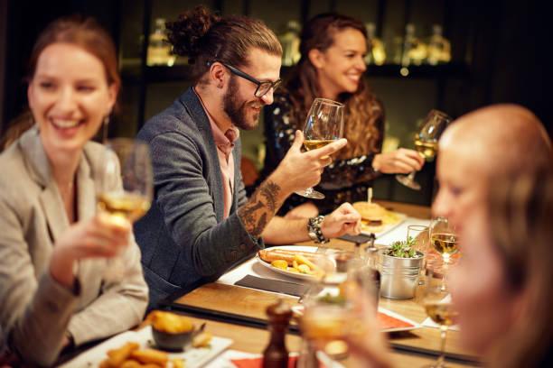 Friends having dinner at restaurant. stock photo