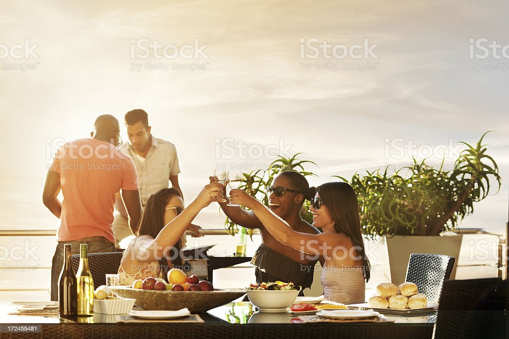 Friends having dinner at sunset royalty-free stock photo