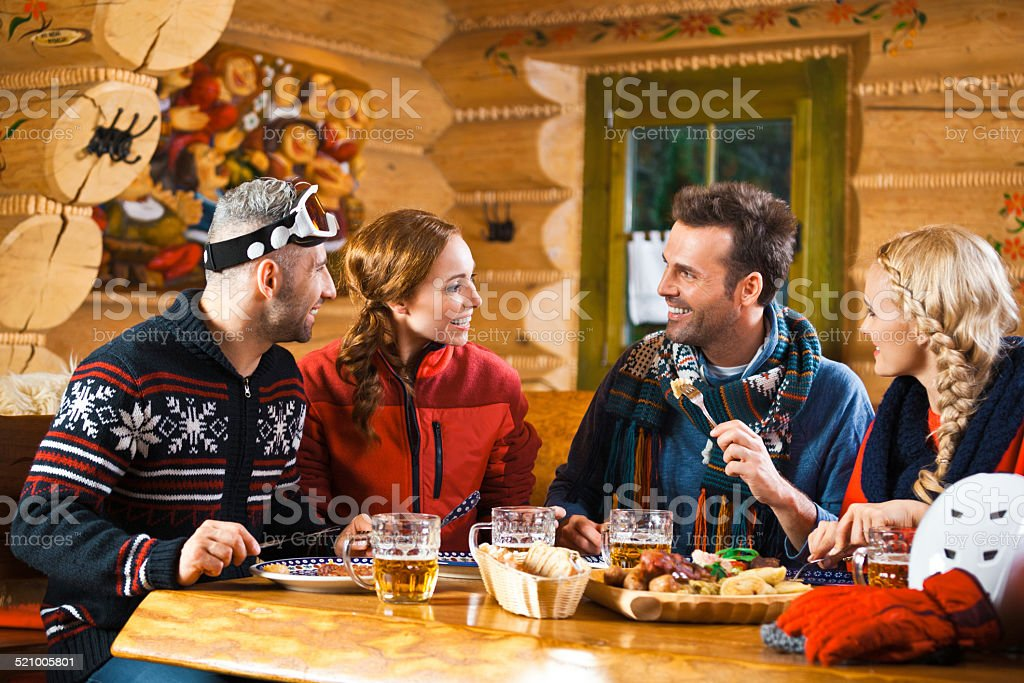 Friends having dinner in restaurant after skiing Two adult couples wearing winter clothes sitting in a mountain restaurant after skiing, talking, enjoying dinner and drinking beer.  Adult Stock Photo