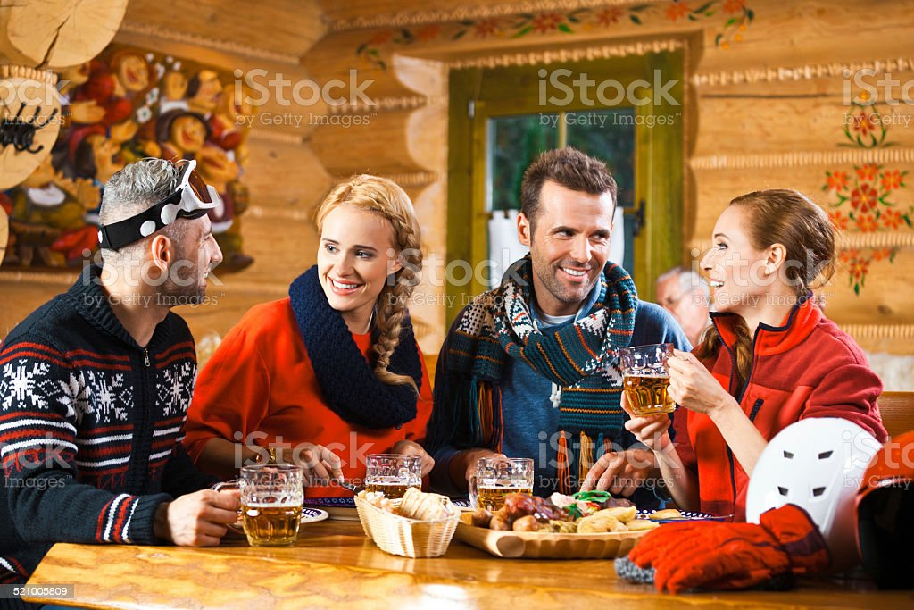 Friends having dinner in restaurant after skiing Two adult couples wearing winter clothes sitting in a mountain restaurant after skiing, having chat, enjoying dinner and drinking beer.  Adult Stock Photo