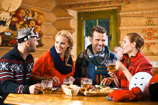 Friends Having Dinner In Restaurant After Skiing Stock Photo - Download Image Now